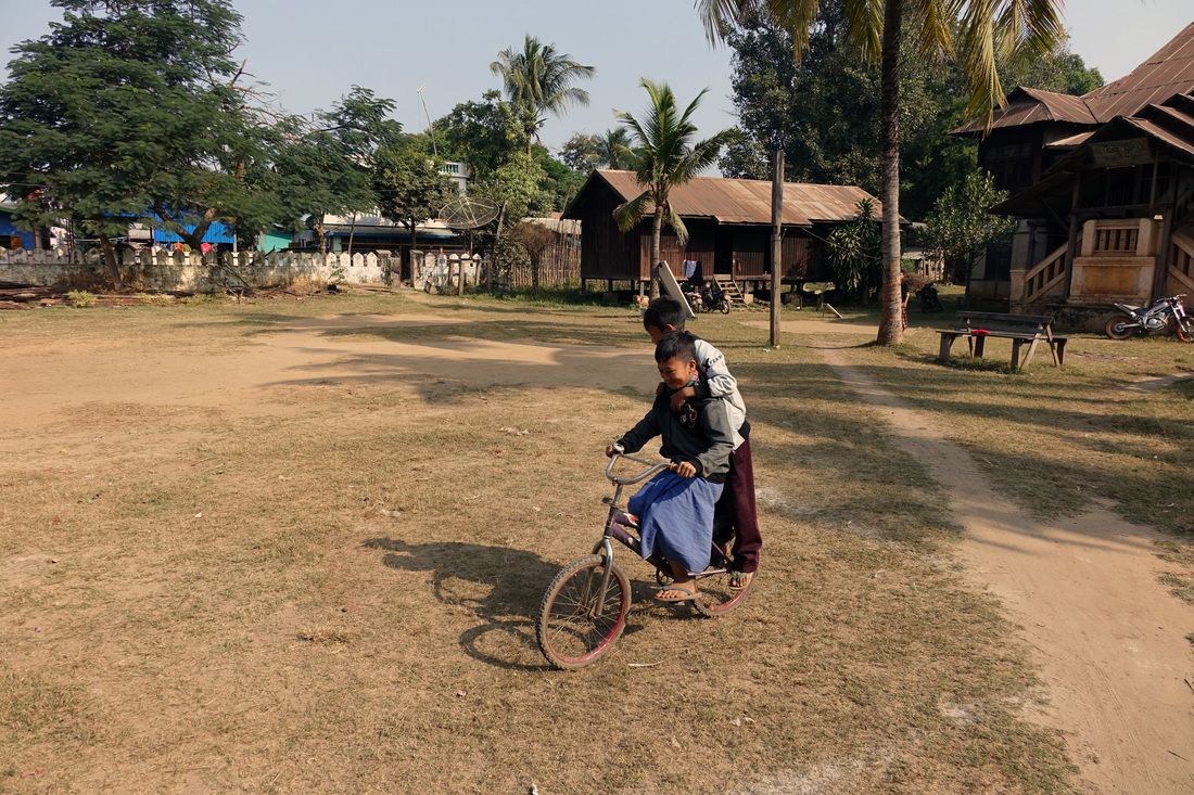 Two Burmese boys share a bike in the village of Kya Hnyat.