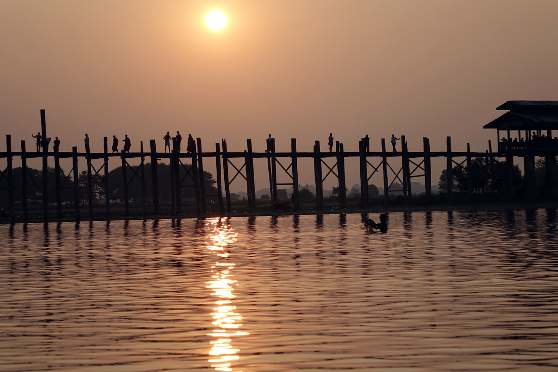 U Bein Bridge, a 1.2 kilometer span that is made from reclaimed teak wood, over Taungthama Lake, a destination at sunset in Amarapura in Burma (Myanmar)