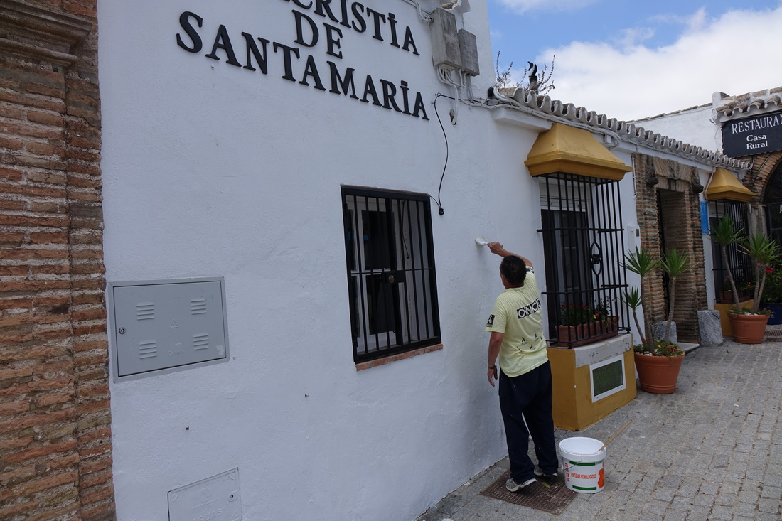 A painter puts on a fresh coat of white paint on a building in Medina-Sidonia in the Andalusian region of Spain.
