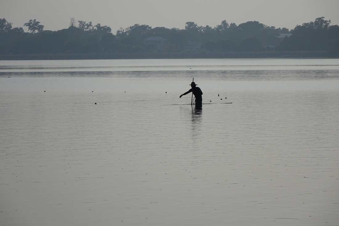 A fisherman casts his net at dusk in a lake just outside Mandalay in Burma