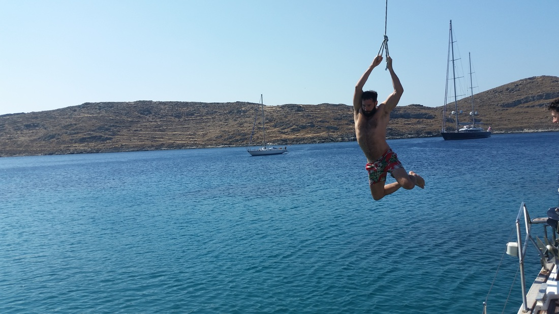Rope swing while sailing in Greece at Kythnos