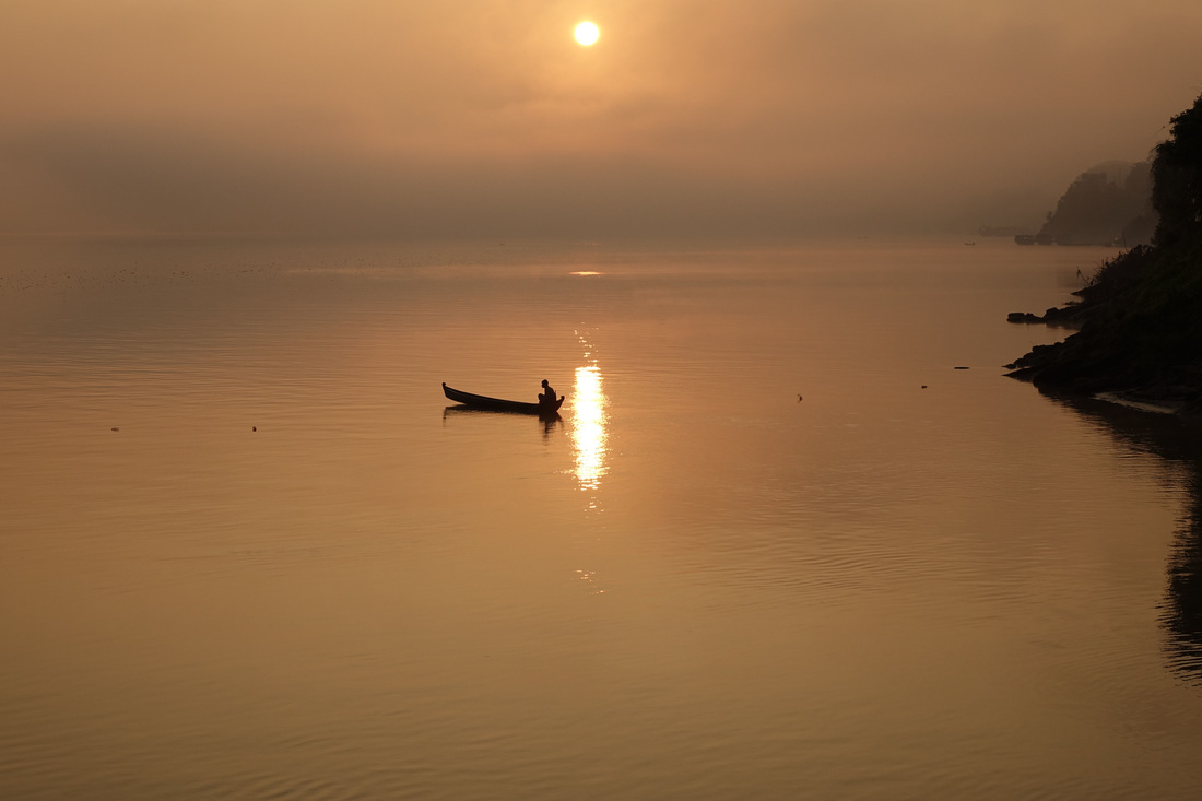 A fisherman starts at sunrise in the Irrawaddy River just south of the village of Bhamo, Myanmar