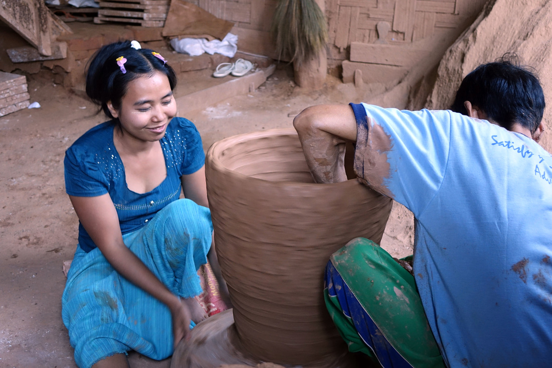 A woman helps her father craft a clay pot in the village of Kyauk Myaung in Burma