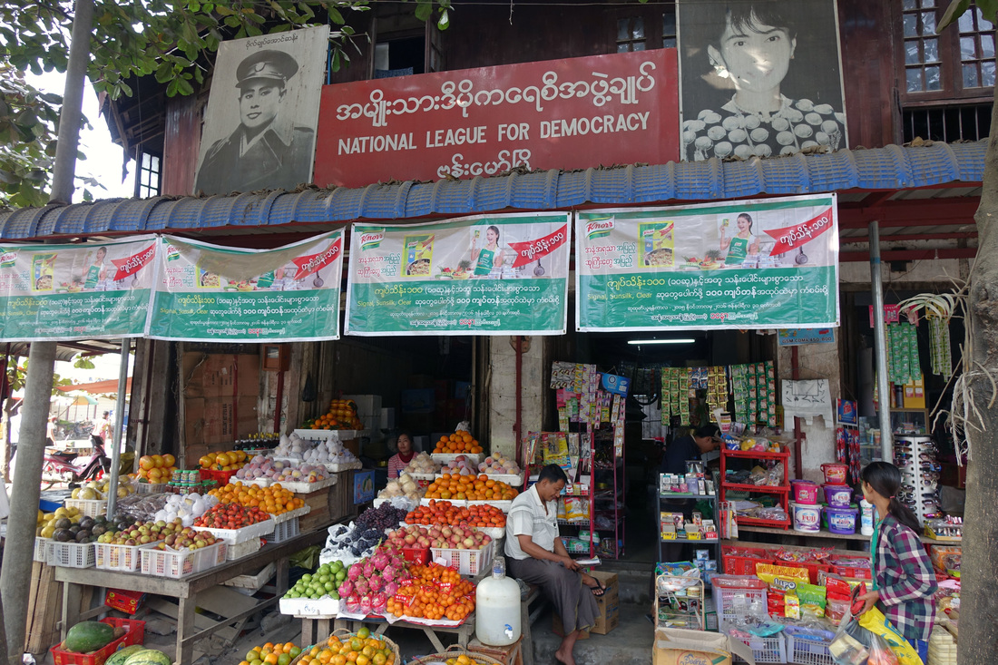 A banner displays the picture of Aung San Suu Kyi at a market in the village of Bhamo in Burma (Myanmar).