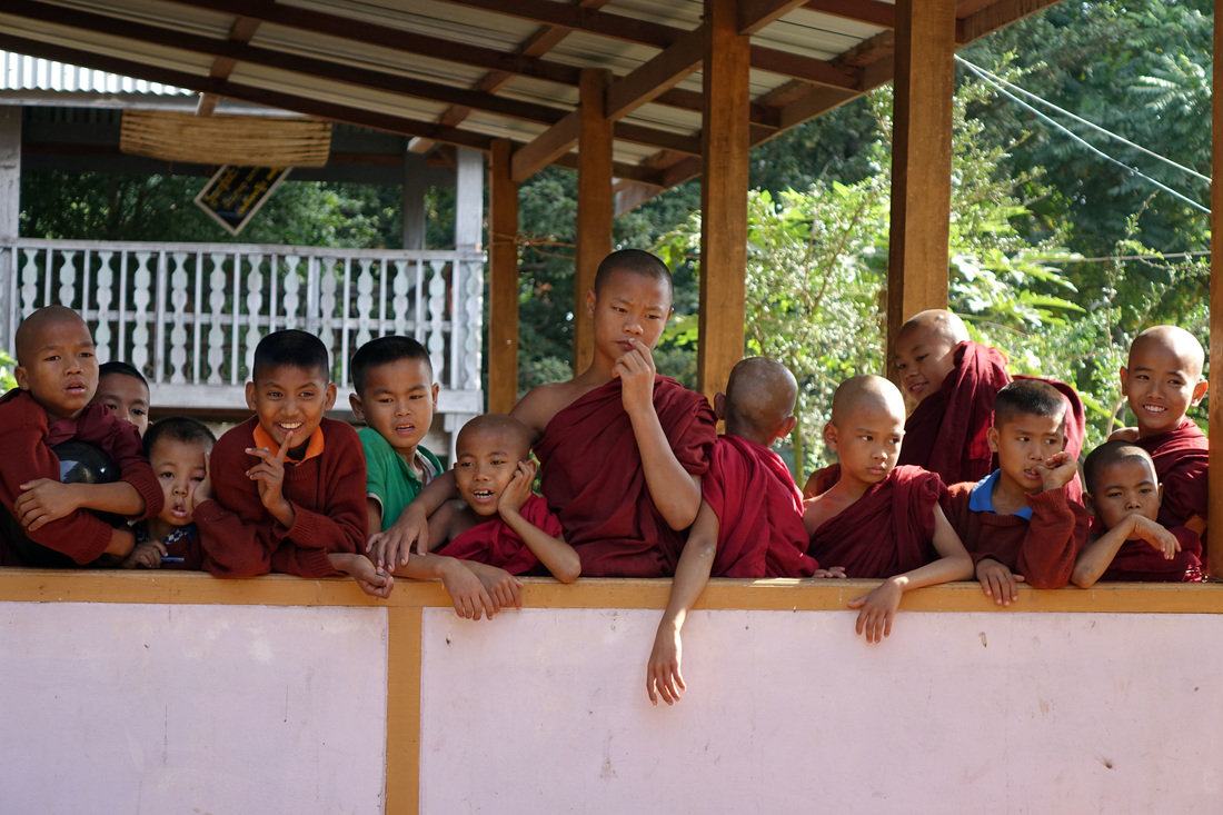 Young monks gather on a porch at a monastery to greet visitors in Kya Hnyat